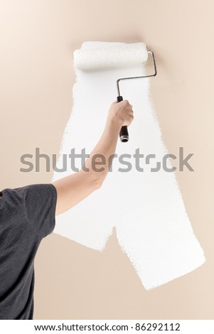 A woman uses a roller to cover a beige wall with white paint. - stock photo