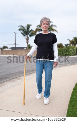 A woman uses a wooden cane to assist her while walking down a sidewalk.
