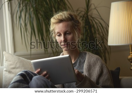 A woman uses an iPad at home - stock photo
