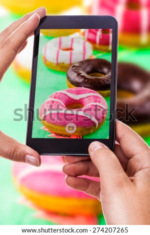 a woman using a smart phone to take a photo of some colorful donuts - stock photo