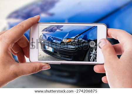 a woman using a smart phone to take a photo of the damage to her car caused by a car crash - stock photo