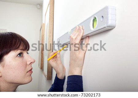 A woman using a spirit level to complete a DIY task.