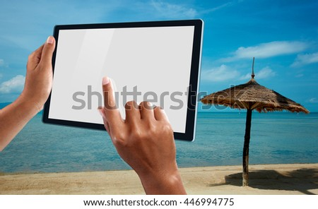 A woman using a tablet at the beach