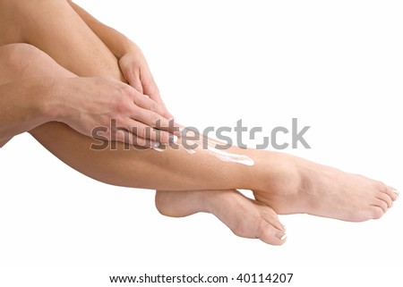 A woman using her hands to rub the lotion into her skin. - stock photo