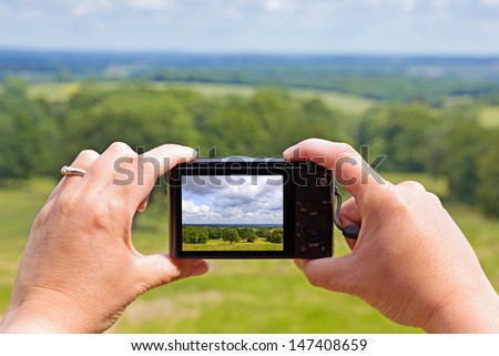 A woman using the rear lcd screen to compose and take a landscape photo with her compact digital camera using liveview. - stock photo