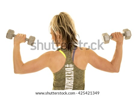 a woman using weights to workout her shoulders, she is showing her back - stock photo