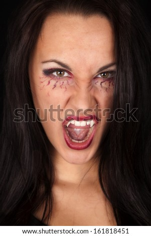 A woman vampire showing off her teeth with her mouth open.