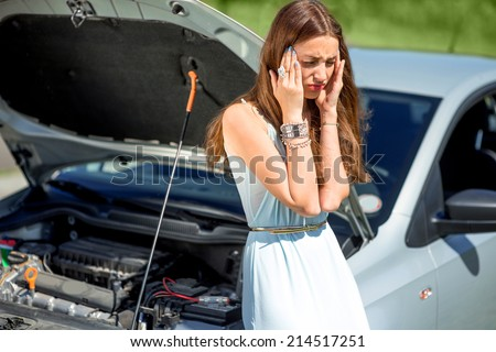 A woman waits for assistance near her car broken down on the road side. - stock photo