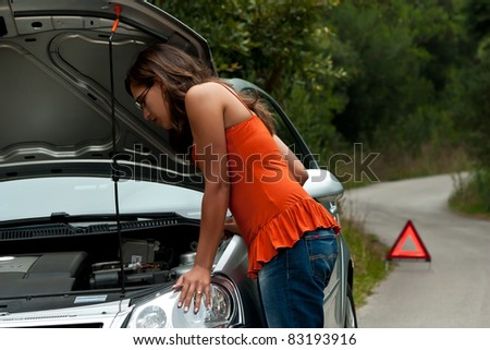 A woman waits for assistance with her car broke down on the road side, after calling for help - stock photo
