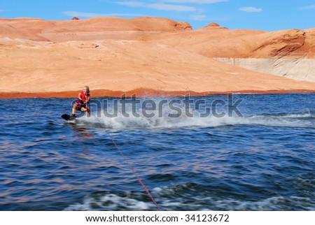A woman wake boarding at Lake Powell - stock photo