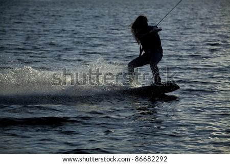 A woman wake boarding on the blue water in the sunset. - stock photo