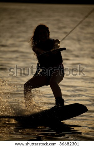 A woman wake boarding on the water with a beautiful sunset. - stock photo
