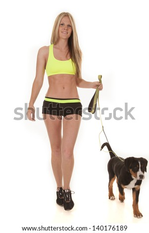 a woman walking and getting exercise for both herself and her Swiss mountain dog. - stock photo
