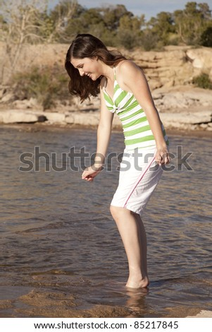 A woman walking in to the water with her feet with a smile on her face.
