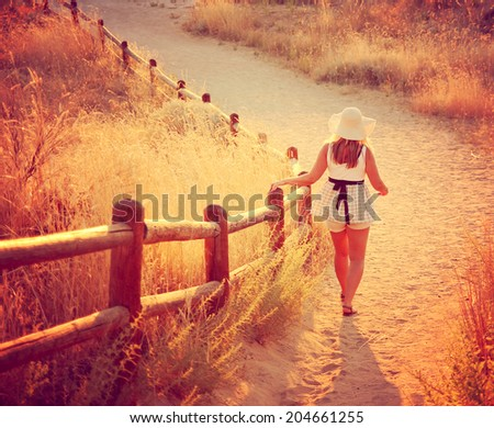 a woman walking on a path during sunset or sunrise toned with an instagram like filter  - stock photo