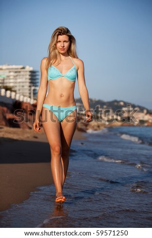 A woman walking on the beach looking at the camera - stock photo