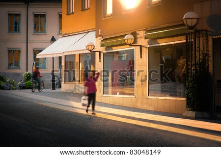 A woman walking with shopping bag in city at sunset - stock photo