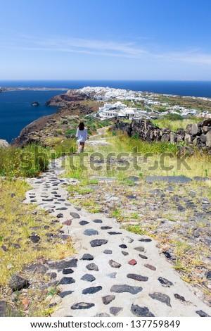 A woman walks along a path in Santorini - stock photo