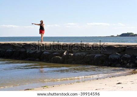 A woman walks down the jetty at the beach pointing to something in the distance. - stock photo