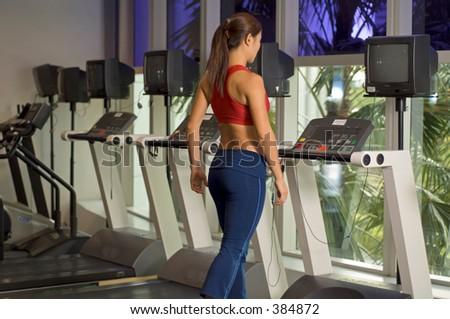 A woman walks on a treadmill - stock photo