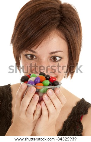 A woman wanting the whole bowl of jelly beans. - stock photo