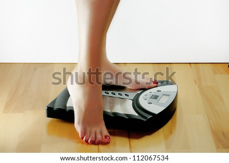 A woman wants to weigh and stands on the scales