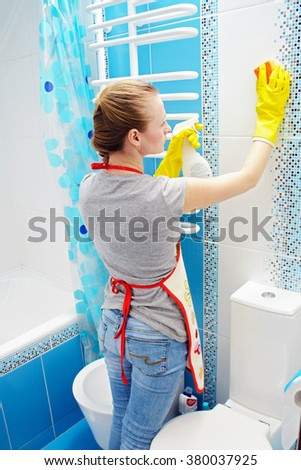 A woman washer is cleaning tiled surface in bathroom. The girl is holding a cleaning spray and a sponge in his hands. Copy space - stock photo