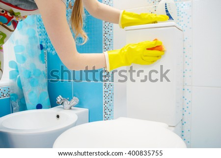 A woman washer is cleaning tiled surface in bathroom. The girl is holding a cleaning spray and a sponge in her hands. Copy space - stock photo