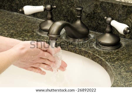 a woman washes her hands with soap and water - stock photo