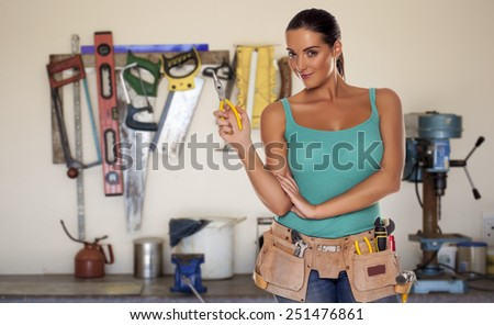 A woman wearing a DIY tool belt full of a variety of useful tools in a workshop. DIY woman. - stock photo