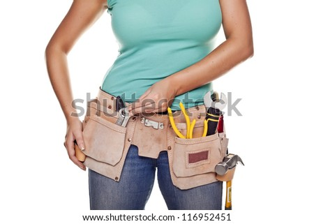 A woman wearing a DIY tool belt full of a variety of useful tools on a white background. Construction woman.