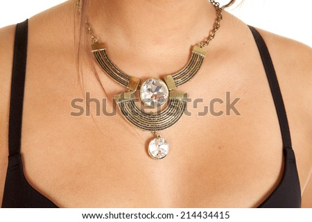 A woman wearing a gold necklace with big rhinestones in the design. - stock photo
