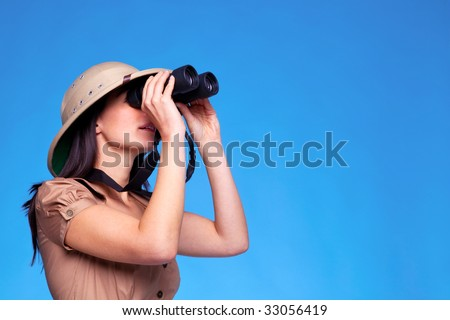 A woman wearing a pith helmet looking through a pair of binoculars, blue background with copy space. - stock photo