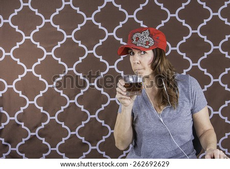A woman wearing a red hat drinking a cocktail out of a straw - stock photo
