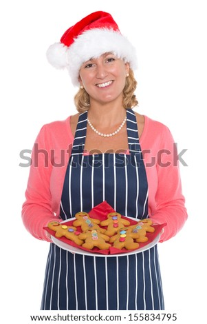 A woman wearing a Santa hat holding a plate of decorated gingerbread men, isolated on a white background. - stock photo