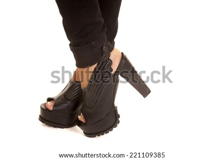 A woman wearing black shoes with wings on the side. - stock photo