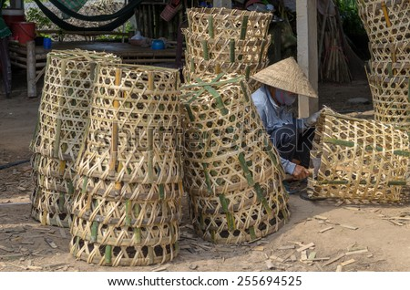 A woman wearing conical working with bamboo baskets at Trade village of Thai My commune, Cu Chi, Ho Chi Minh city, Vietnam - stock photo