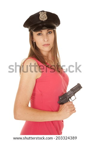 A woman wearing her police hat holding on to a weapon in her fancy dress.