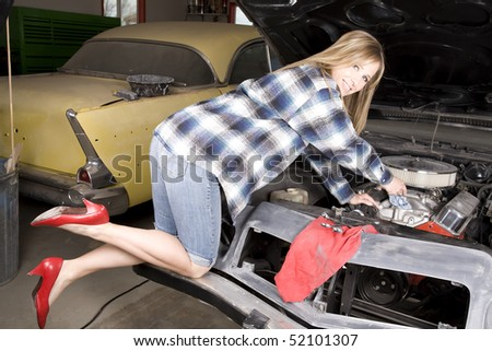 A woman wearing her red heels while she is working on her car engine.