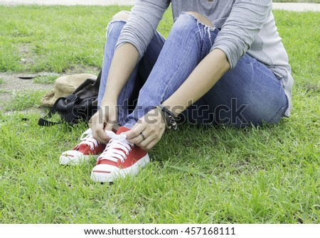 A woman wearing jean are the red sneakers lace up in the green lawn. - stock photo