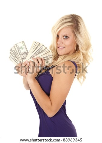 A woman wearing purple holding on to a fan full of money with a smile on her face. - stock photo