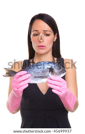 A woman wearing rubber gloves holding a raw fish, isolated on a white background - stock photo