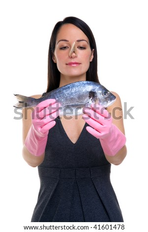 A woman wearing rubber gloves with a clothes peg on her nose holding a fish out in front of her, focus is on her face. - stock photo