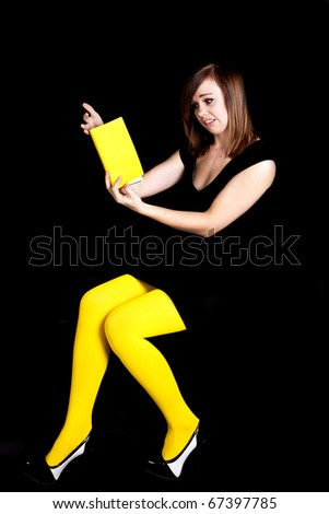 A woman wearing yellow tights in front of a black background not liking this part of the book.