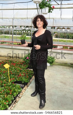A woman who buys plants in a garden center