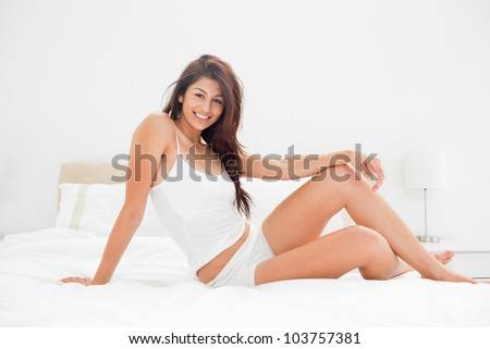 A woman who is smiling and sitting on the width of the bed with a raised knee and one arm placed across the knee while the other arm supports her. - stock photo