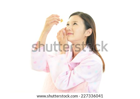 A woman who put in the eye drops - stock photo