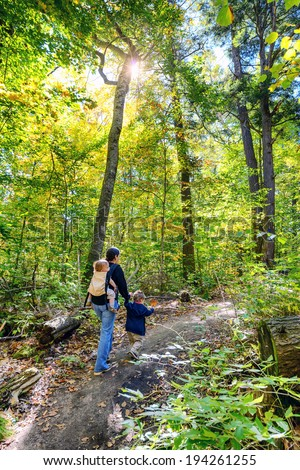 A woman with a baby in a back carrier holding the hand of a toddler as they walk on a trail in a forest during the autumn season.  The toddler holds on to a maple leaf.  - stock photo