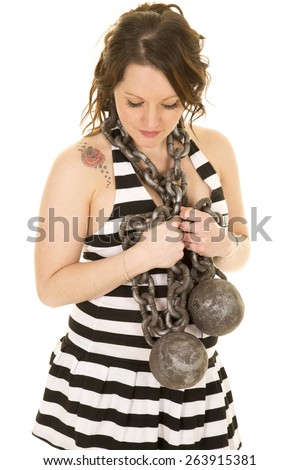 A woman with a ball and chain wrapped around her neck, in her prison clothes looking down. - stock photo