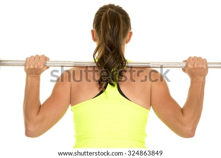 A woman with a bar across her back lifting weights.